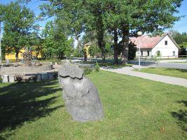 Mälestuskiv asub Rakke keskväljakul, purskaevu juures, üle tee asub raamatukogu. Foto: Heiki Koov, august 2010.
